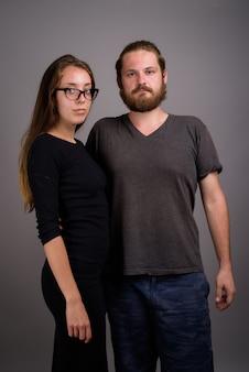 Retrato, de, pareja joven, juntos, contra, fondo gris