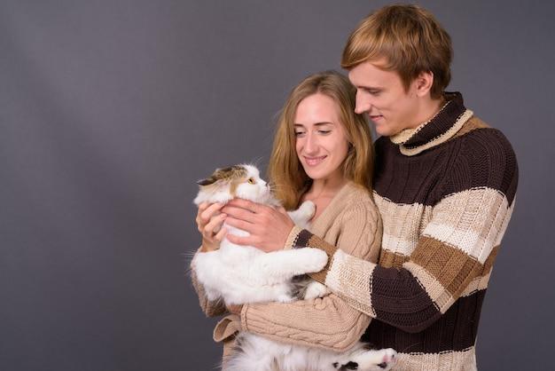 Retrato, de, pareja joven, juntos, tenencia, gato persa