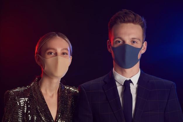Retrato de pareja joven con máscaras faciales y mirando a la cámara mientras posa en la fiesta de pie contra el fondo negro