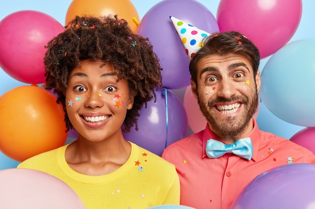 Retrato de pareja joven posando rodeada de globos de colores de cumpleaños