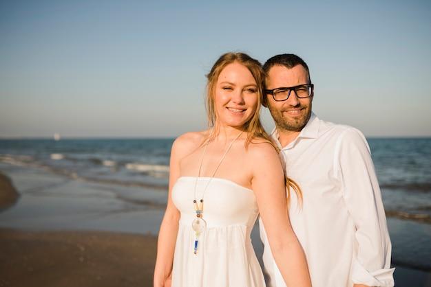 Retrato de la pareja joven sonriente que se coloca cerca del mar en la playa