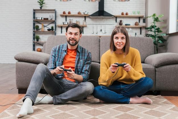Retrato de la pareja joven sonriente que se sienta en el piso que juega al videojuego