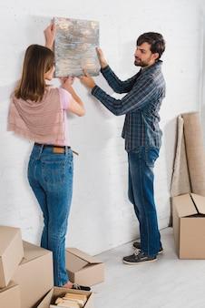 Retrato de una pareja joven sosteniendo un marco pintado sobre la pared blanca en su nueva casa