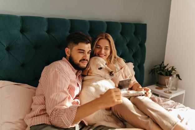 Retrato de pareja joven y su doglying en cama de color esmeralda. marido y mujer miran una foto memorable con una sonrisa.