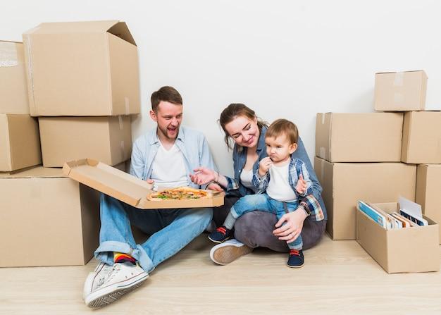Retrato de una pareja joven con su hijo disfrutando la pizza en su nueva casa