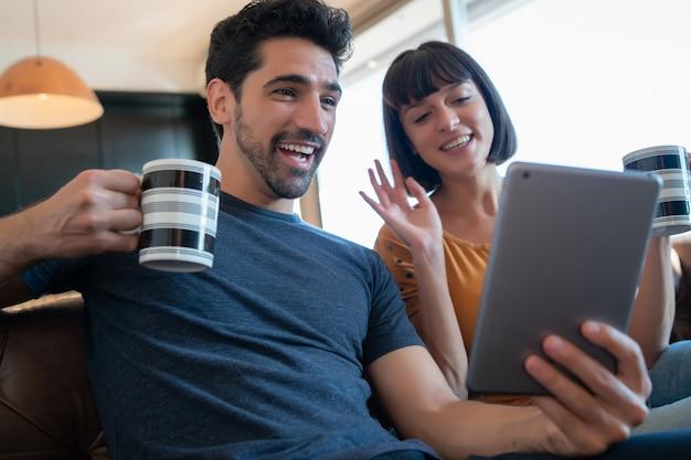 Retrato de pareja joven en una videollamada con tableta digital mientras está sentado en el sofá en casa