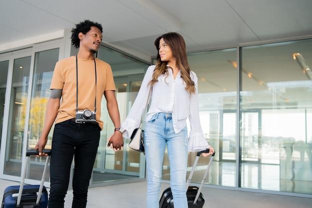 Retrato de pareja de jóvenes turistas llevando maleta mientras camina al aire libre en la calle. concepto de turismo.