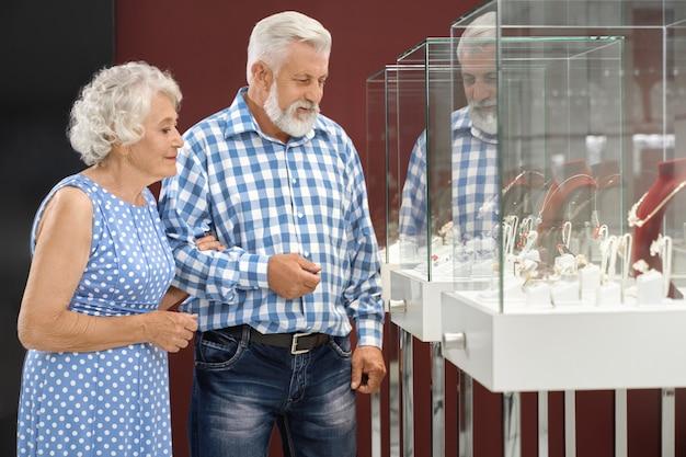 Retrato de pareja madura comprando joyas en la tienda de lujo