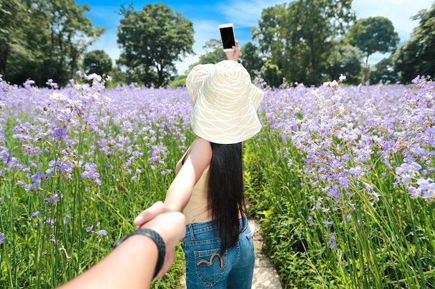 Retrato de una pareja de la mano entre el campo con cresta de flores naga en la naturaleza, mientras que la mujer que usa el teléfono celular se toma photo