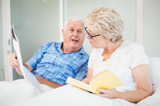 Retrato, de, pareja mayor, lectura, en cama