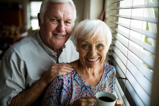Retrato, de, pareja mayor, posición, cerca, ventana, en casa