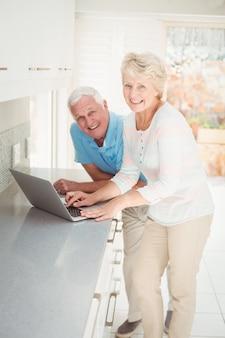 Retrato, de, pareja mayor, usar la computadora portátil, en, cocina