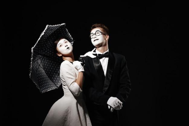 Retrato de pareja mimo con paraguas sobre fondo negro. hombre con esmoquin y gafas y mujer con vestido blanco. espacio para texto