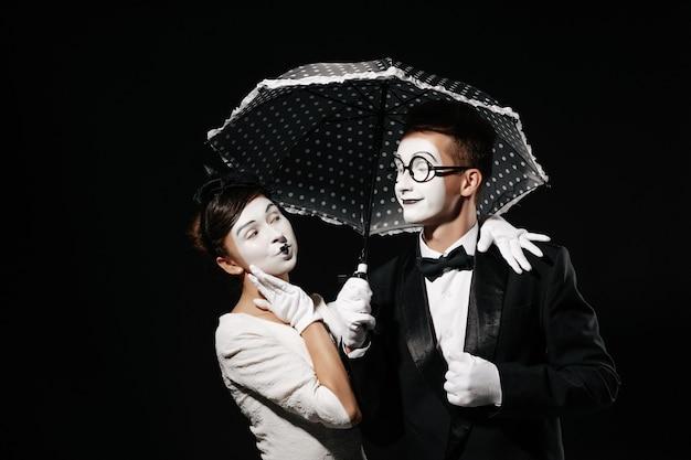 Retrato de pareja mimo con paraguas sobre fondo negro. hombre en esmoquin y gafas y mujer en vestido blanco