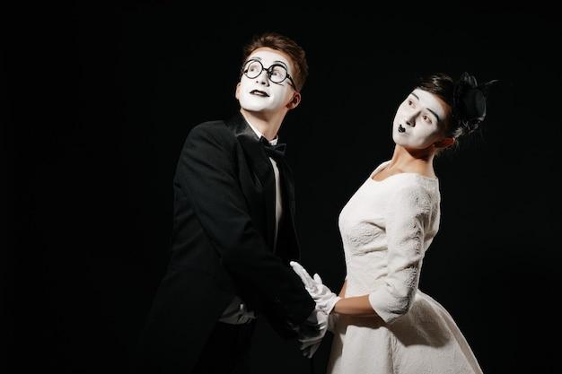 Retrato de pareja mimo sobre fondo negro. hombre en esmoquin y gafas y mujer en vestido blanco