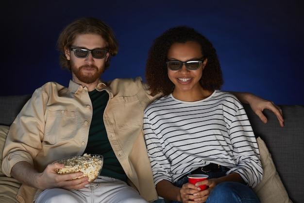 Retrato de una pareja moderna de raza mixta viendo películas y con gafas estéreo mientras disfruta de la cita en el cine