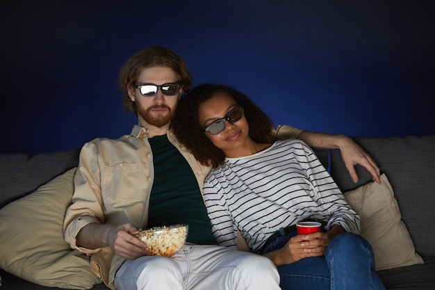 Retrato de una pareja moderna de raza mixta viendo películas y con gafas estéreo mientras está sentado en el sofá en una habitación oscura