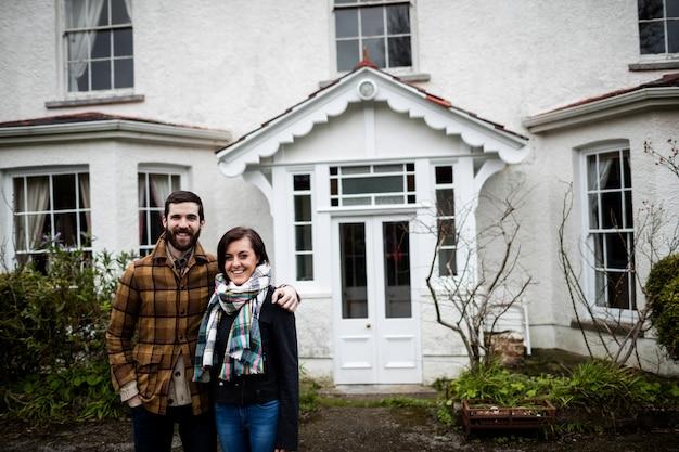 Retrato de pareja de pie cerca de una casa nueva