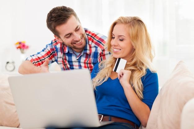 Retrato de pareja con portátil y tarjeta de crédito en el salón
