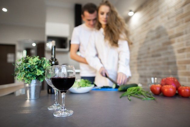 Retrato de pareja romántica en la cocina en casa. la mujer rubia con el pelo largo corta el pepino. un hombre abrazando a una mujer desde el costado