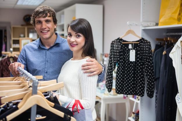 Retrato de pareja seleccionando un vestido mientras compra ropa