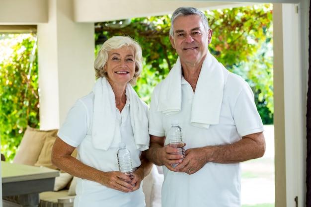 Retrato de pareja senior activa sosteniendo botellas de agua