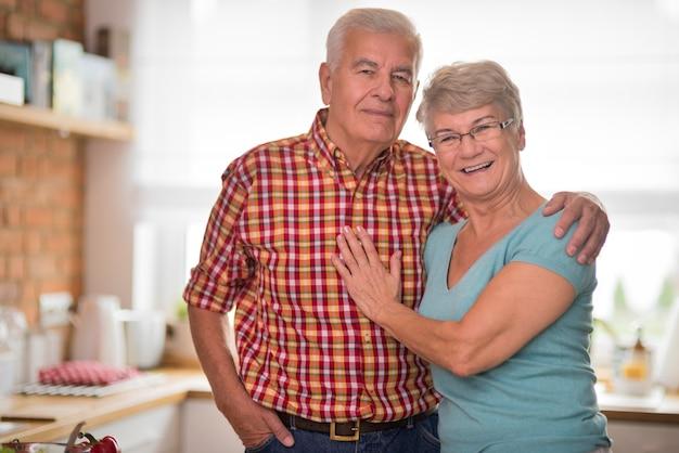 Retrato de pareja senior alegre en la cocina