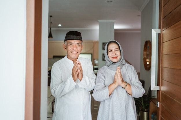 Retrato de pareja senior asiática musulmana de pie en la puerta de entrada esperando a que venga la familia