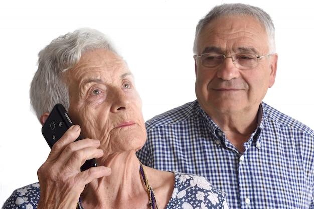 Retrato de una pareja senior hablando por teléfono móvil