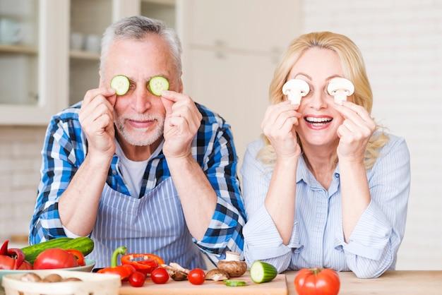 Retrato de una pareja senior que cubre sus ojos con rodajas de pepino y champiñones