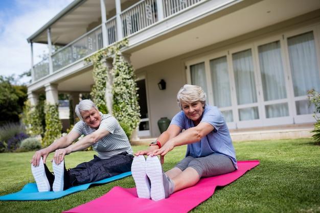 Retrato de pareja senior realizando ejercicios de estiramiento en estera del ejercicio