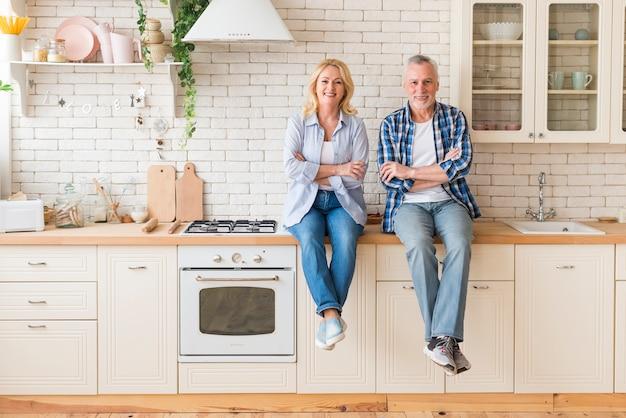 Retrato de una pareja senior con sus brazos cruzados sentado en el mostrador de la cocina