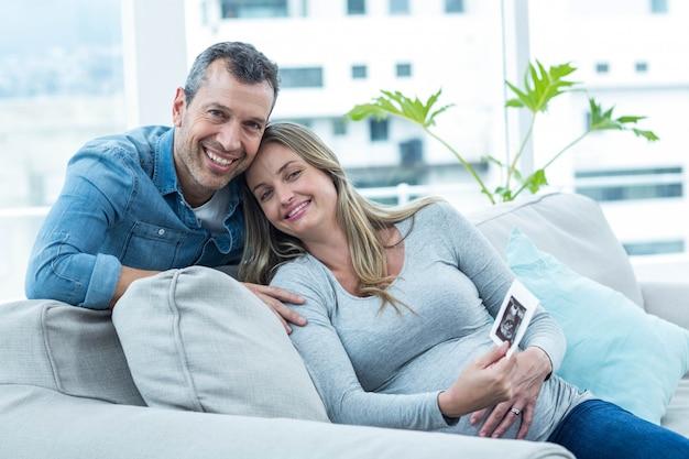 Retrato de pareja sentada en el sofá y con ecografía