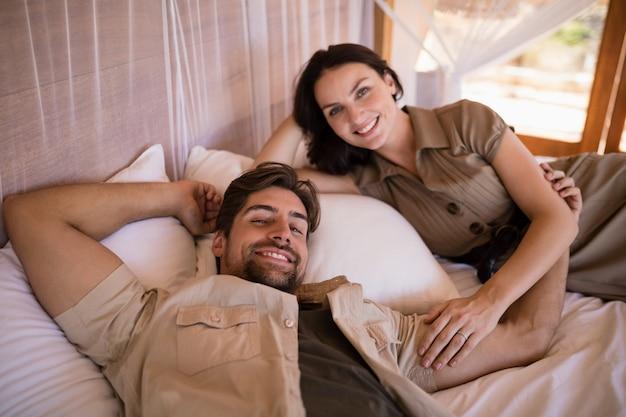 Retrato de pareja sonriendo mientras está acostado en la cama con dosel