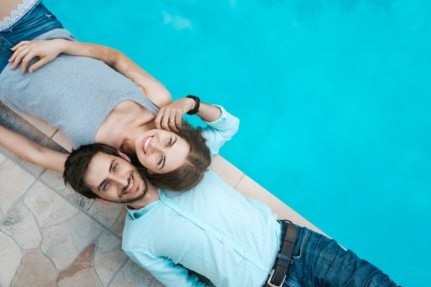 Retrato de pareja sonriente acostado vestido cerca de la piscina. se adoran