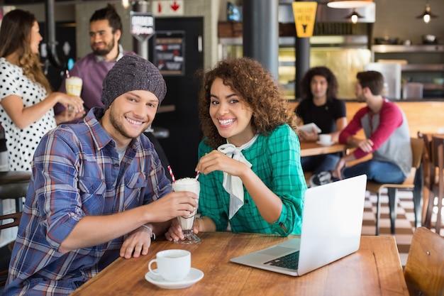 Retrato de pareja sonriente con batido mientras está sentado en el restaurante