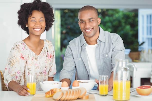 Retrato de la pareja sonriente desayunando en la cocina