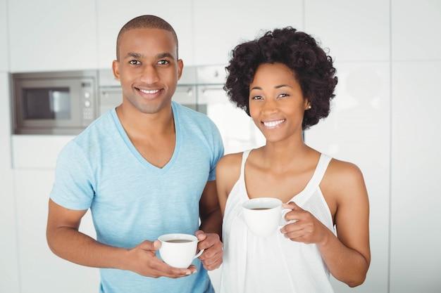Retrato de pareja sonriente sosteniendo tazas en la cocina