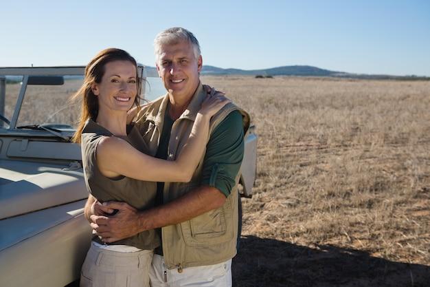 Retrato de pareja sonriente en vehículo en campo