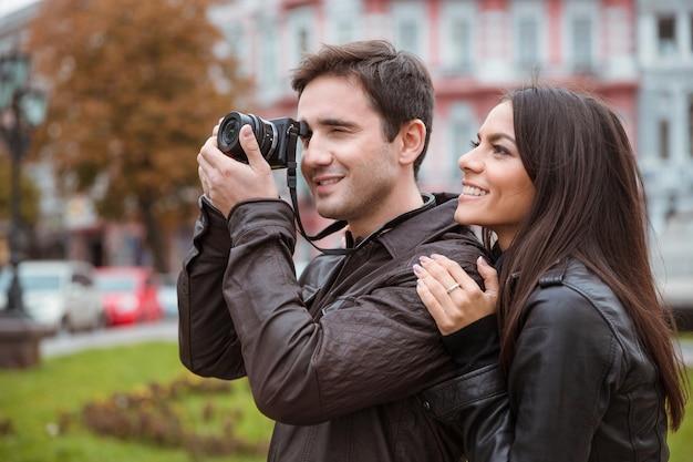 Retrato de una pareja sonriente viajando y haciendo fotos en el frente en la vieja ciudad europea