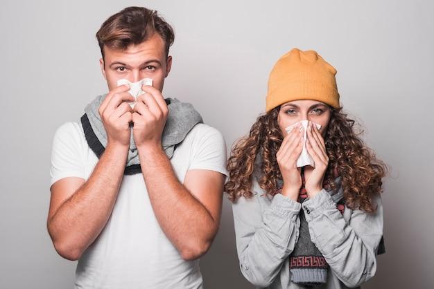 Retrato de pareja soplar la nariz con papel de seda sobre fondo gris