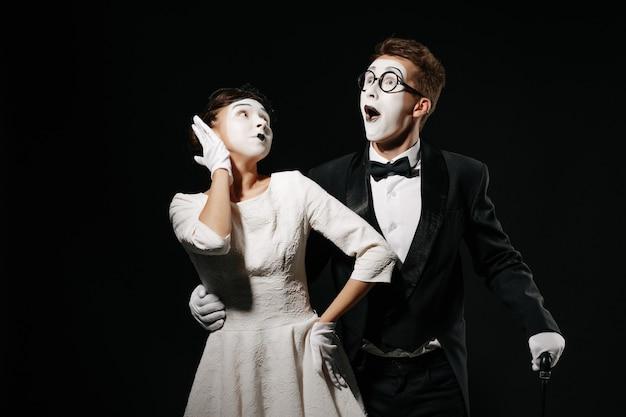 Retrato de pareja sorprendida mimo sobre fondo negro. hombre en esmoquin y gafas y mujer en vestido blanco