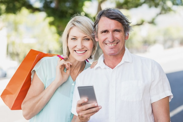 Retrato de pareja con teléfono celular y bolsas de compras