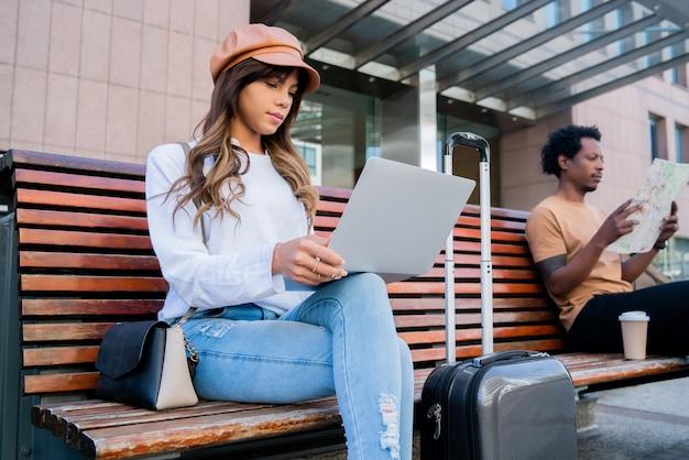 Retrato de una pareja de turistas sentados en un banco fuera del aeropuerto o de la estación de tren