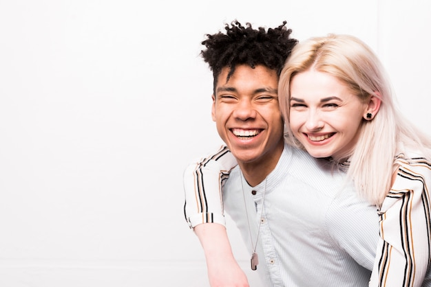 Retrato de los pares adolescentes interraciales sonrientes que miran la cámara contra el contexto blanco