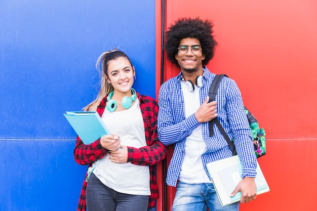 Retrato de los pares adolescentes sonrientes jovenes que sostienen los libros que se oponen a la pared roja y azul