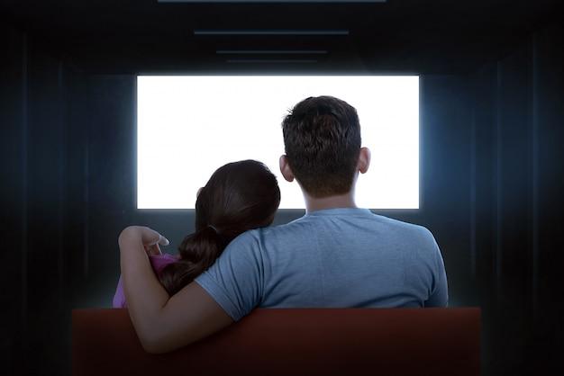 Retrato de los pares asiáticos que se sientan en el sofá que ve la tv en blanco