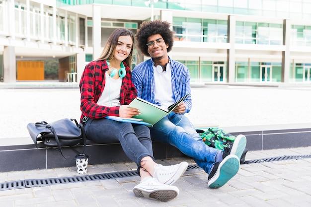 Retrato de los pares étnicos multi jovenes que se sientan delante del edificio de la universidad que estudian juntos