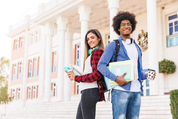 Retrato de los pares jovenes confiados que sostienen los libros y la taza de café disponible que se colocan delante del edificio de la universidad