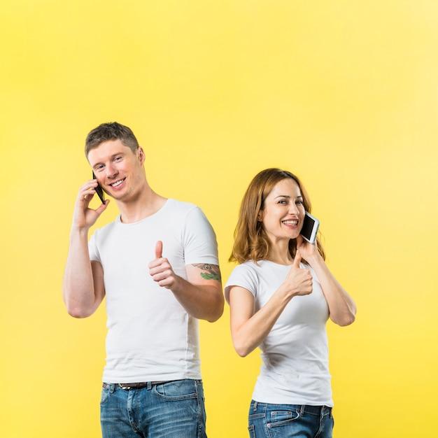 Retrato de los pares jovenes sonrientes que hablan en el teléfono móvil que muestra el pulgar encima de la muestra contra el contexto amarillo